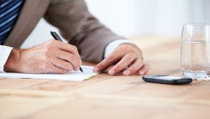 Cropped image of a businessman writing on a piece of paper with his cellphone in front of him